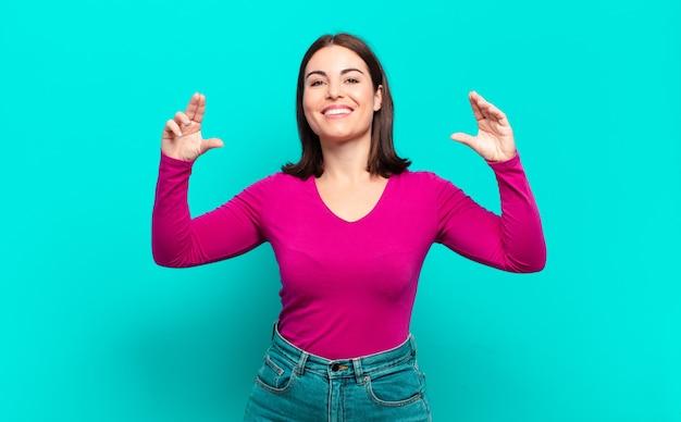 Mulher jovem, muito casual, emoldurando ou delineando o próprio sorriso com as duas mãos, parecendo positiva e feliz, quadro de bem-estar