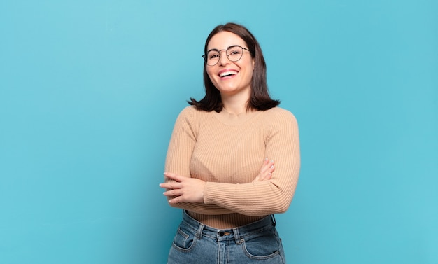 Mulher jovem, muito casual, rindo alegremente com os braços cruzados, em uma pose relaxada, positiva e satisfeita