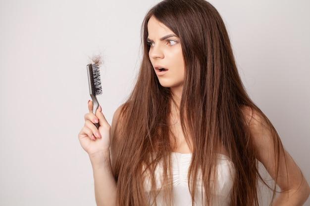 Mulher jovem muito chateada com o pente e o problema da perda de cabelo.