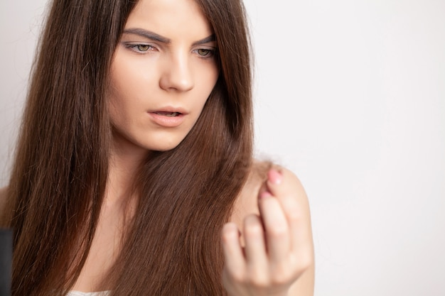 Mulher jovem muito chateada tem um problema de queda de cabelo