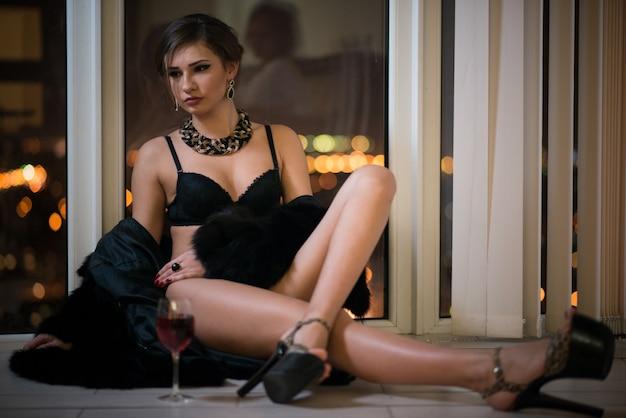 Mulher jovem muito elegante com maquiagem de salto alto à noite e sentada perto da janela panorâmica com vista para a cidade à noite com uma taça de vinho. conceito de luxo e hotel cinco estrelas