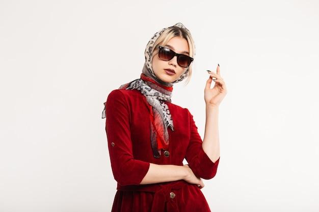 Mulher jovem muito elegante em elegantes óculos de sol na moda vestido cor de vinho com lindo lenço de leopardo na cabeça posando.