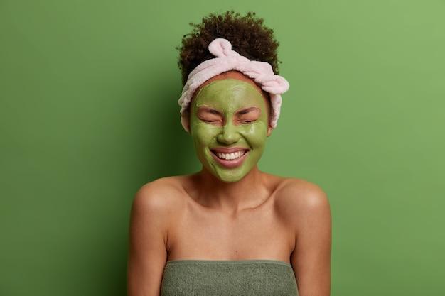 Mulher jovem muito feliz aplica máscara de argila natural para reduzir acnes, sorri amplamente, tem dentes brancos perfeitos, penteava os cabelos cacheados, tiara, mostra os ombros nus, isolada na parede verde