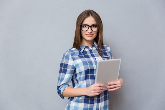 Mulher jovem muito feliz com cabelo comprido, camisa xadrez e óculos segurando um tablet