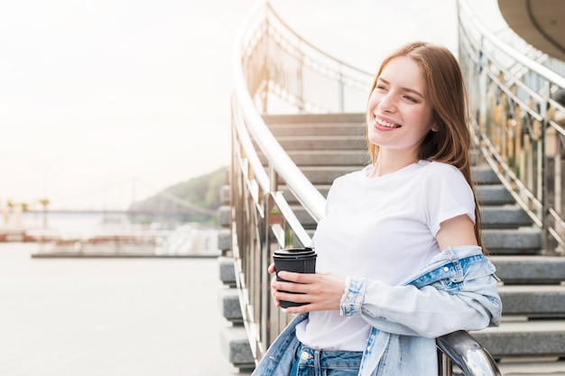 Mulher jovem muito sorridente, apoiando-se no parapeito metálico com segurando copo descartável