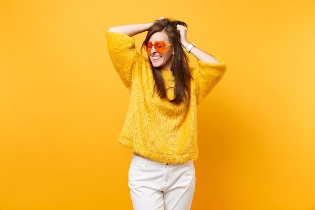 Mulher jovem muito sorridente com os olhos fechados, no suéter de pele e óculos coração laranja agarrando-se à cabeça isolada no fundo amarelo brilhante. emoções sinceras de pessoas, conceito de estilo de vida. área de publicidade.