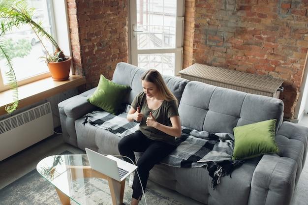 Mulher jovem, mulher de negócios à procura de emprego em casa, parece na tela do computador, monitor.