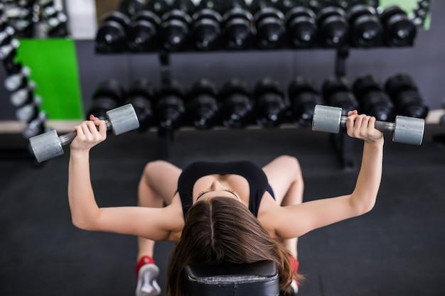 Mulher jovem muscular desportiva sexy malhando com dois halteres prateados