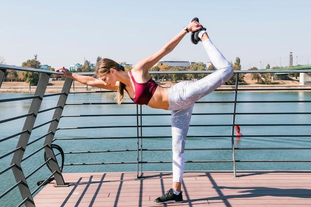 Mulher jovem, músculos esticando, durante, exercício, em, ao ar livre