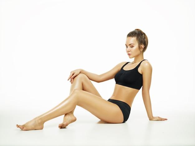 Mulher jovem musculosa ou atleta posando no estúdio isolado no fundo branco. modelo caucasiano em forma com corpo perfeito. fitness, esporte, beleza, conceito de pele fresca.