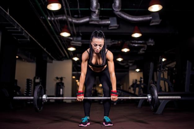 Mulher jovem musculoso fitness fazendo exercícios de levantamento terra pesados no ginásio