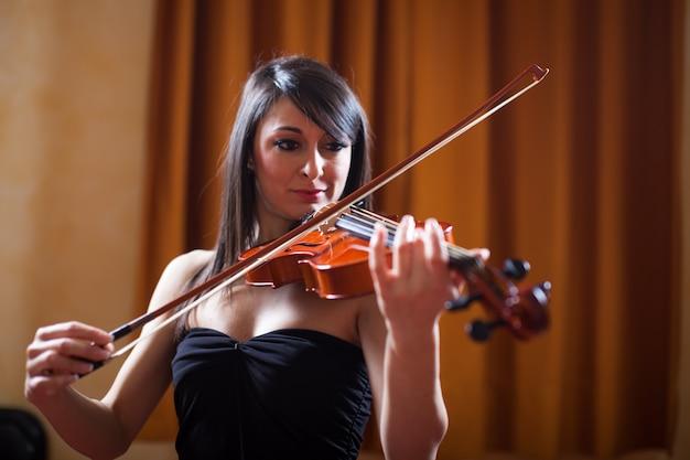 Mulher jovem músico tocando seu violino