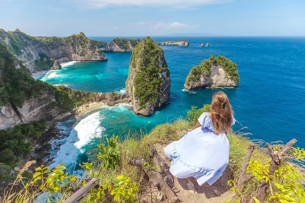 Mulher jovem na bela costa rochosa na ilha thousand, na ilha nusa penida