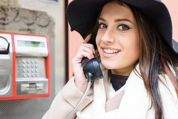 Mulher jovem na cabine telefônica