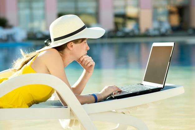 Mulher jovem na cadeira de praia na piscina, trabalhando em um computador laptop conectado à internet sem fio, digitando texto nas teclas em um resort de verão