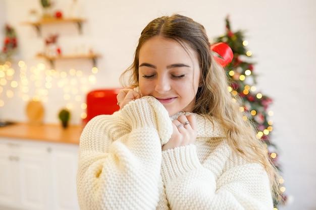 Mulher jovem na cozinha decorada de natal