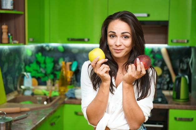 Mulher jovem na cozinha segurando frutas nas mãos