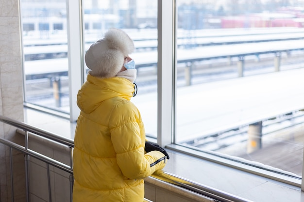 Mulher jovem na estação ferroviária com uma máscara protetora no rosto no passageiro de roupas de inverno