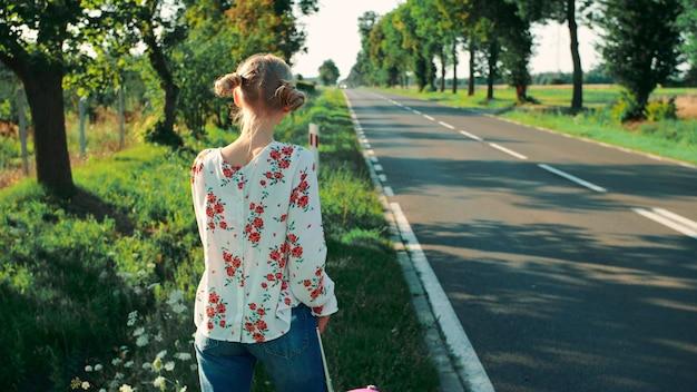 Mulher jovem na estrada rural vista traseira de uma jovem fêmea com uma mala vermelha em pé na estrada ...
