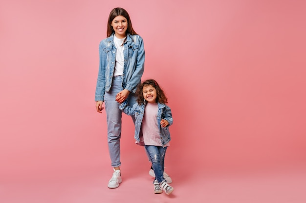Mulher jovem na moda de mãos dadas com a filha encaracolada. foto de estúdio de mãe atraente e criança pré-adolescente dançando juntos.