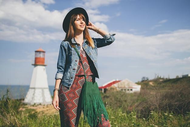 Mulher jovem na natureza, farol, roupa boêmia, jaqueta jeans, chapéu preto, sorridente, feliz, verão, acessórios elegantes