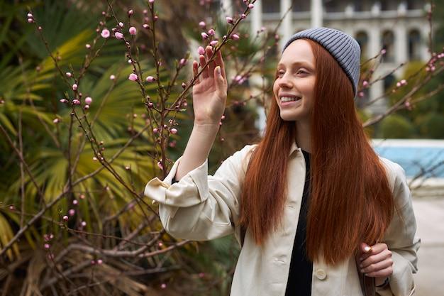 Mulher jovem na primavera jardim primavera moda ruiva feminina gosta de sentir o cheiro de flores desabrochando na árvore, olhando para o lado, sorrindo, caminhando sozinha de bom humor, construindo ao fundo