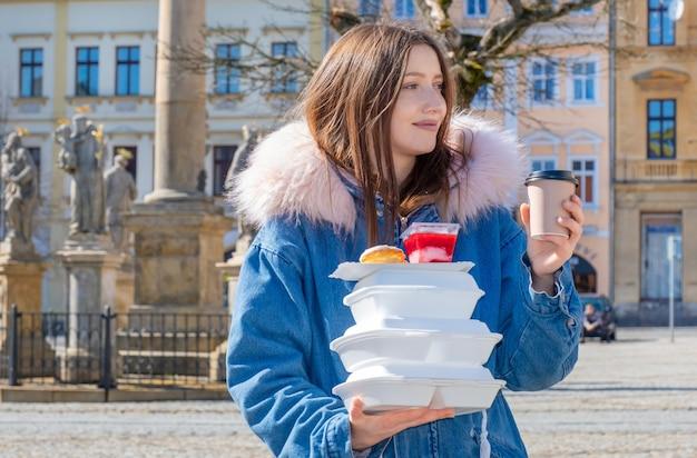 Mulher jovem na rua com um casaco com lancheiras e entrega de café e comida de entrega.