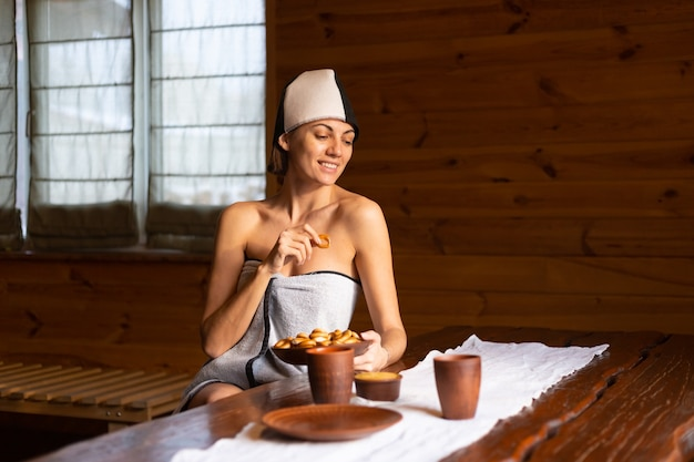 Mulher jovem na sauna com um boné na cabeça sentada a uma mesa com bagels redondos, mel e chá, desfrutando de um dia de bem-estar Foto gratuita