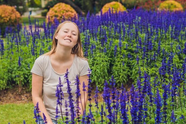 Mulher jovem na superfície de flores azul salvia farinacea florescendo no jardim