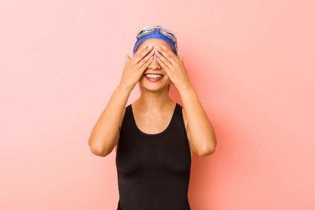 Mulher jovem nadador árabe isolada cobre os olhos com as mãos, sorri amplamente esperando por uma surpresa.