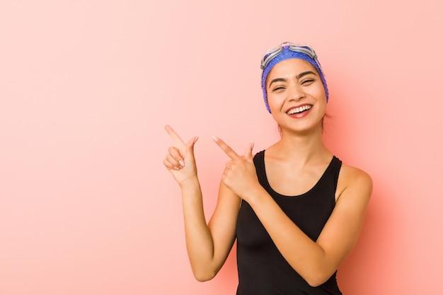 Mulher jovem nadador árabe isolado apontando com o dedo indicador para um espaço de cópia, expressando emoção e desejo.