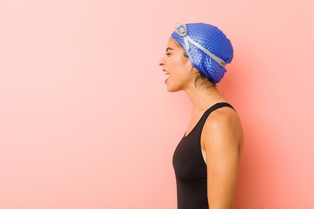 Mulher jovem nadador árabe isolado gritando para um espaço de cópia