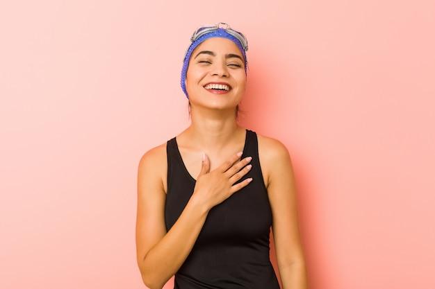Mulher jovem nadador árabe isolado ri alto, mantendo a mão no peito.