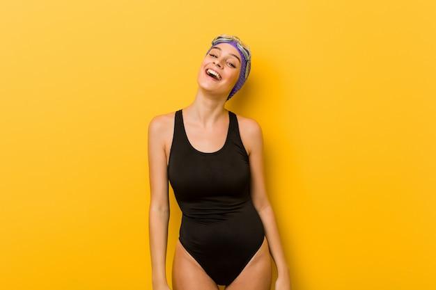 Mulher jovem nadador relaxado e feliz rindo, pescoço esticado, mostrando os dentes