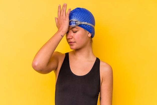 Mulher jovem nadadora venezuelana isolada em fundo amarelo, esquecendo de algo, batendo na testa com a palma da mão e fechando os olhos.