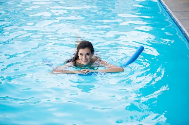 Mulher jovem nadando com tubo inflável na piscina