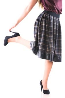 Mulher jovem não identificada em uma saia longa e salto alto, posando em um fundo branco.