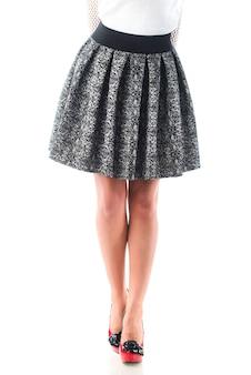 Mulher jovem não identificada posando com uma saia elegante e um suéter em uma parede branca
