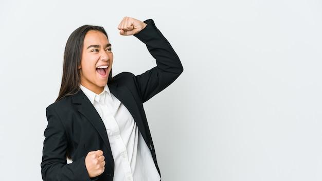 Mulher jovem negócios asiáticos isolada no branco levantando o punho após uma vitória, o conceito de vencedor.