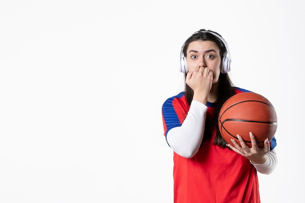 Mulher jovem nervosa de frente com roupas esporte e basquete