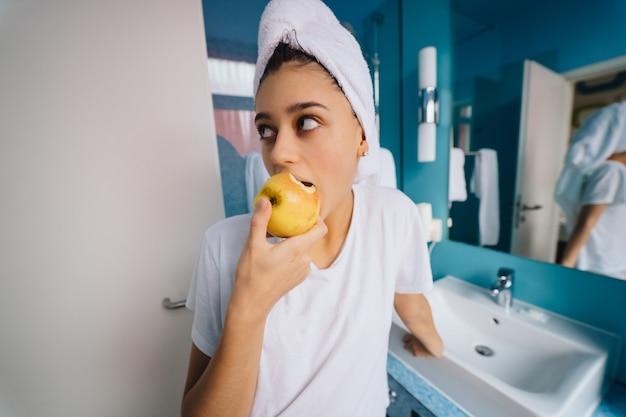 Mulher jovem no banheiro, comendo maçã