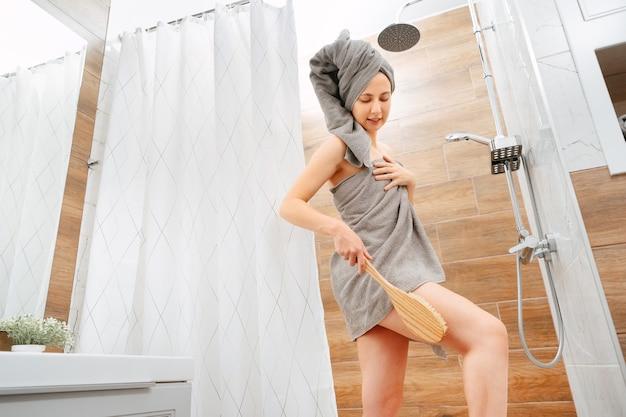 Mulher jovem no banheiro penteia as pernas delgadas com uma escova de madeira contra a celulite e a secura. conceito de atendimento domiciliar.