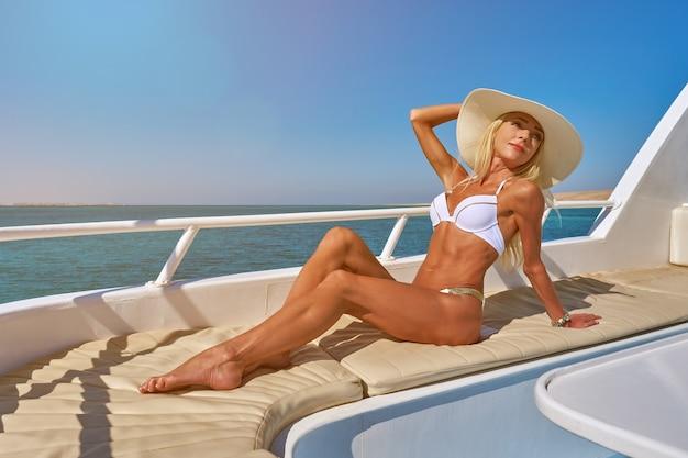 Mulher jovem no convés de um barco em mar aberto em um dia ensolarado de verão