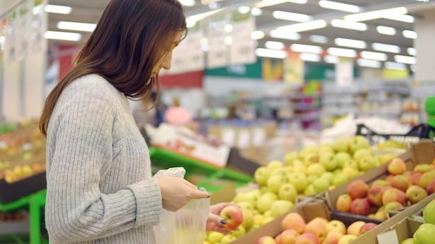 Mulher jovem no departamento de vegetais de um supermercado está colhendo maçãs.