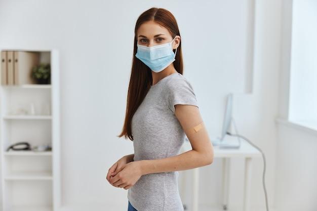 Mulher jovem no hospital com máscara médica no rosto e passaporte bactericida de gesso