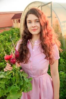 Mulher jovem no jardim, usando um chapéu e segurando um monte de rabanetes frescos em uma noite ensolarada