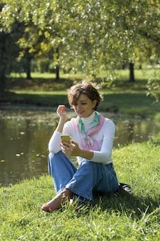 Mulher jovem no parque fala por telefone celular. retrato de linda garota em estilo francês.