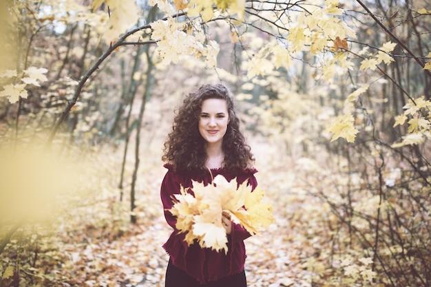 Mulher jovem no parque outono segurando folhas de bordo