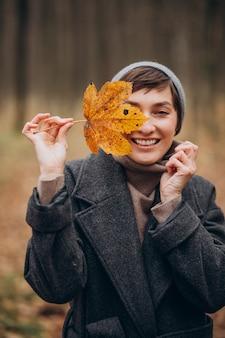 Mulher jovem no parque outono segurando uma folha perto do rosto