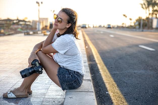Mulher jovem no verão de shorts e camiseta sentada na calçada com uma câmera ao pôr do sol